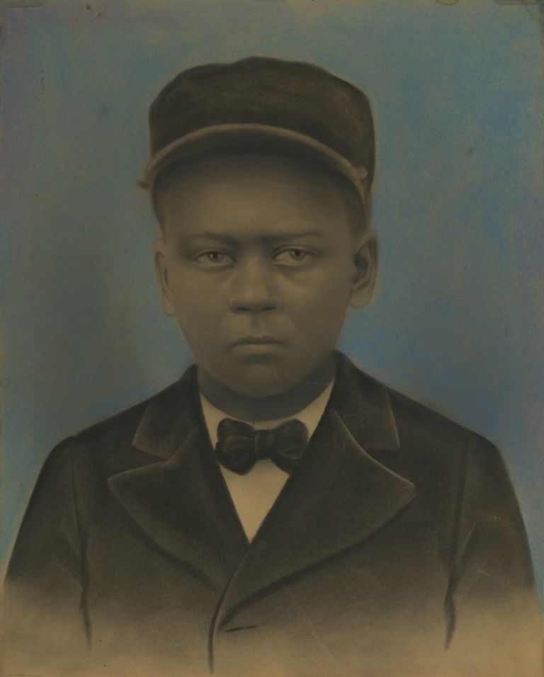 HAUNTING HAND-COLORED PORTRAIT OF A YOUNG AFRICAN-AMERICAN IN A PULLMAN PORTER UNIFORM.