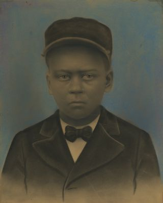 HAUNTING HAND-COLORED PORTRAIT OF A YOUNG AFRICAN-AMERICAN IN A PULLMAN PORTER UNIFORM